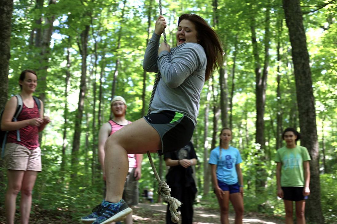 Camper swinging on low ropes element