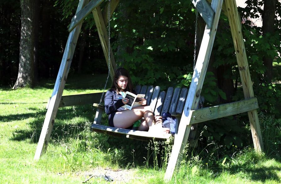 Camper relaxing and reading on swing