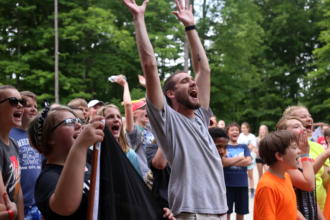 Staff and Campers Excited and hands up